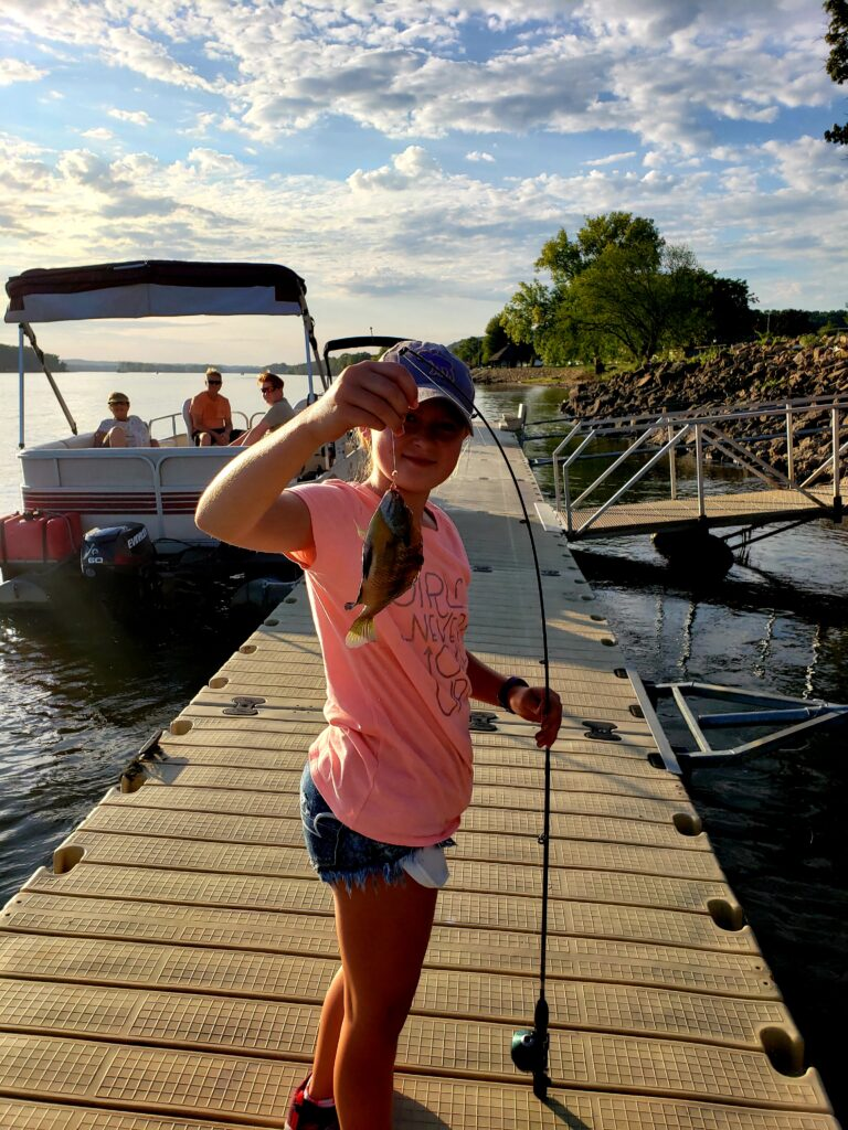Young Girl showing her catch with pontoon in background