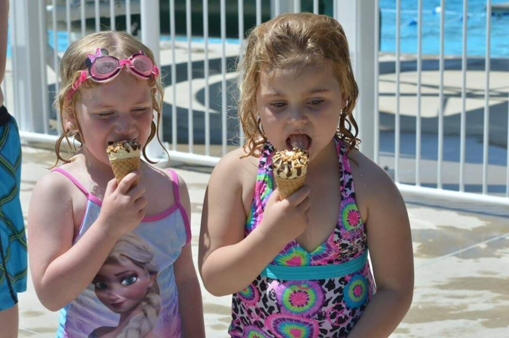 little girls eating ice-cream cones at pool