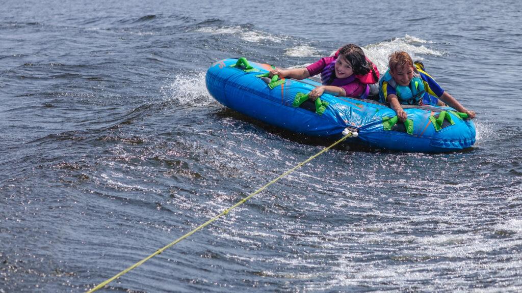 Children,Tubing,Behind,Motorboat,On,Lake,In,Summer